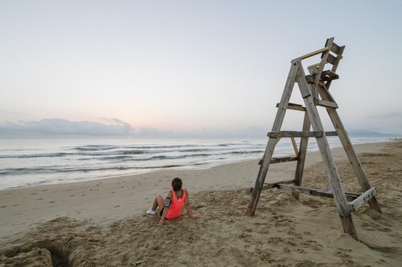 girl-watching-the-sunrise-sitting-on-the-beach