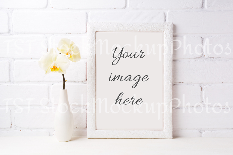 Free White frame mockup with soft yellow orchid in vase (PSD Mockups)