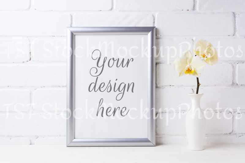 Free Silver frame mockup with soft yellow orchid in vase (PSD Mockups)
