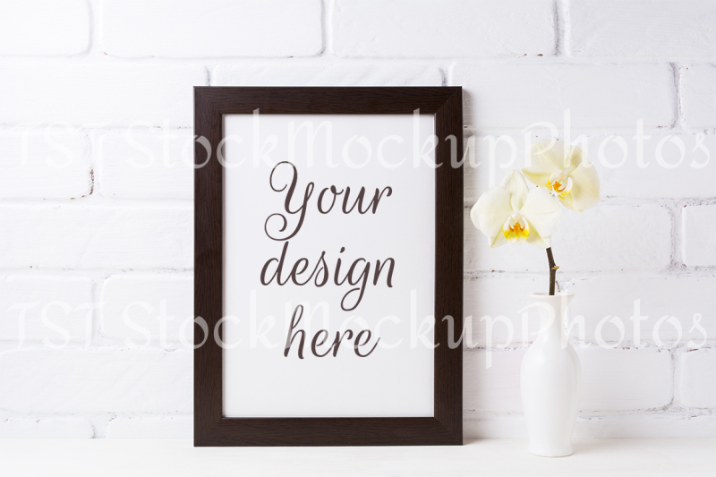 Free Black brown frame mockup with soft yellow orchid in vase (PSD Mockups)