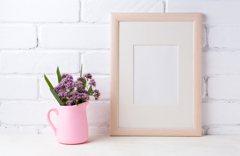 Free Wooden frame mockup with purple flowers in pink pitcher (PSD Mockups)