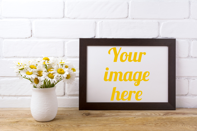 Free Black brown landscape frame mockup with chamomile bouquet in rustic vase (PSD Mockups)