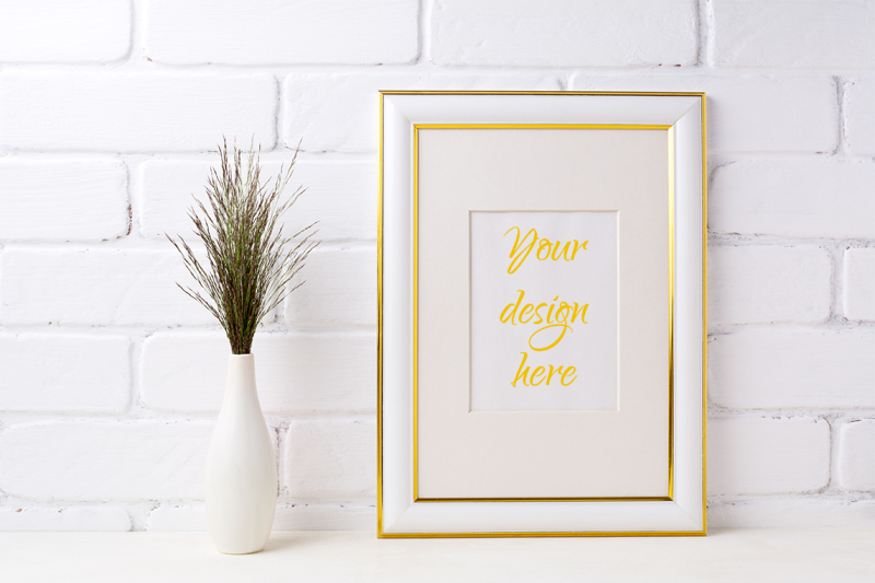 Free Gold decorated frame mockup with dark grass in vase near brick wall. (PSD Mockups)