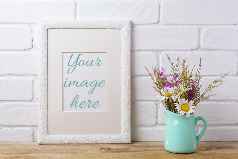 Free White frame mockup with chamomile and purple field flowers in mint pitcher. (PSD Mockups)