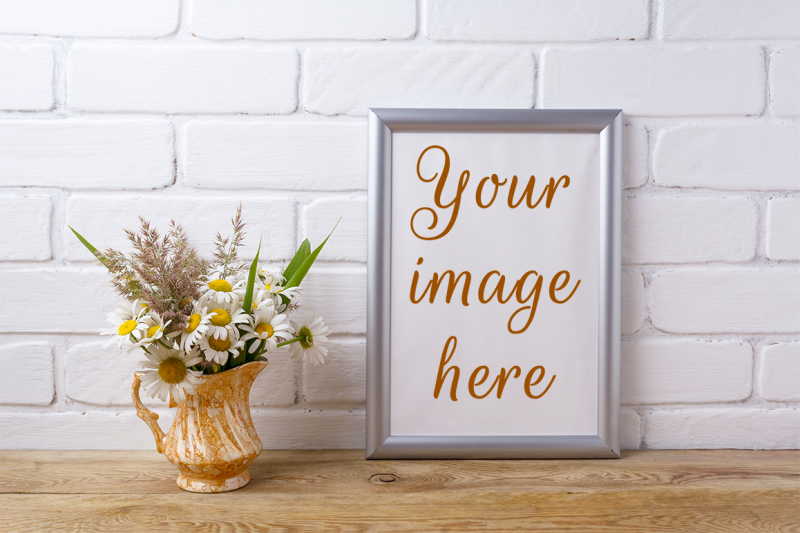 Free Silver frame mockup with chamomile and grass in golden pitcher. (PSD Mockups)